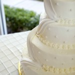 3 Three Tier ivory wedding cake with flowers and swag