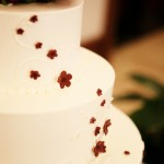 4 Tier white wedding cake with red roses and flower detail