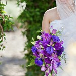 Bride in white one shoulder wedding gown and cascading purple flowers J Squared Events