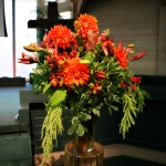 Orange and green altar floral arrangements by Anne Mendenhall